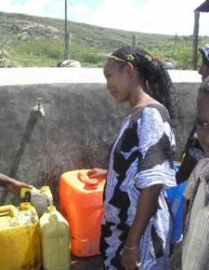 Kvinna som tappar upp vatten vid en utomhuskran