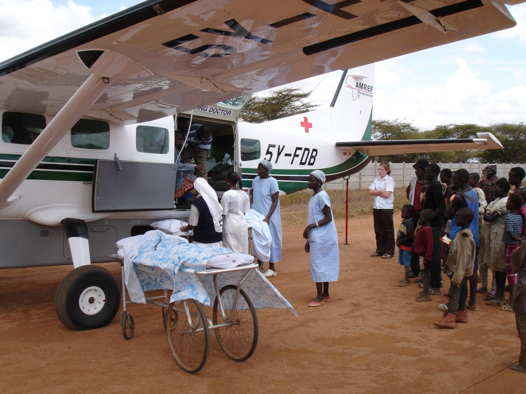 Patient på bår, två sjuksköterskor, AMREF-plan som landat på landsbygden, samt åskådare