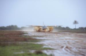 AMREF-plan som startar från en regndränkt landningsbana av jord