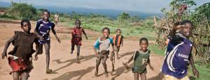 barn som springer efter en land rover i ett afrikanskt landskap