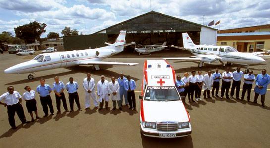 En ambulans, flera flygplan och personal utanför hangaren