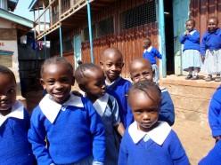 Skolbarn i blå skoluniform på sin skolgård
